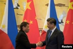 Tổng thống Philippines Rodrigo Duterte (trái) bắt tay Chủ tịch Trung Quốc Tập Cận Bình sau một lễ ký kết ở Bắc Kinh ngày 20/10/2016.