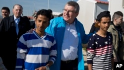 IOC President Thomas Bach, center, walks with two young refugees with former IOC President Jacques Rogge in the background, during their visit to a refugee camp in Athens, Greece, Jan, 28, 2016.