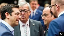 Greek Prime Minister Alexis Tsipras, left, speaks with, from left, European Commission President Jean-Claude Juncker, French President Francois Hollande and Belgian Prime Minister Charles Michel during a meeting of eurozone heads of state at the EU Council building in Brussels on Sunday, July 12, 2015. (AP Photo/Geert Vanden Wijngaert)
