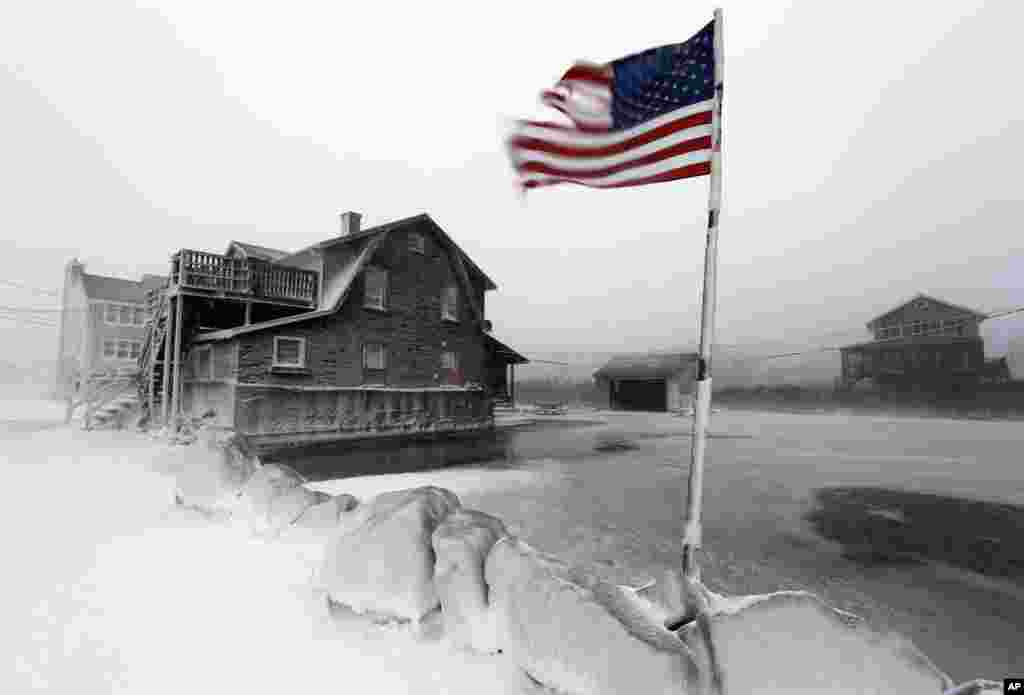A tattered flag flies by a flooded yard along the shore in Scituate, Massachusetts, Jan. 3, 2014. A blustering winter storm dropped nearly two feet of snow just north of Boston.