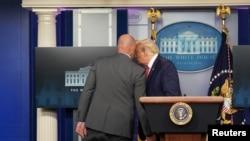 Un agent des services secrets chuchote à l'oreille du président américain Donald Trump avant de l'escorter hors d'un briefing sur la maladie COVID-19 à la Maison Blanche à Washington, aux États-Unis, le 10 août 2020. REUTERS/Kevin Lamarque