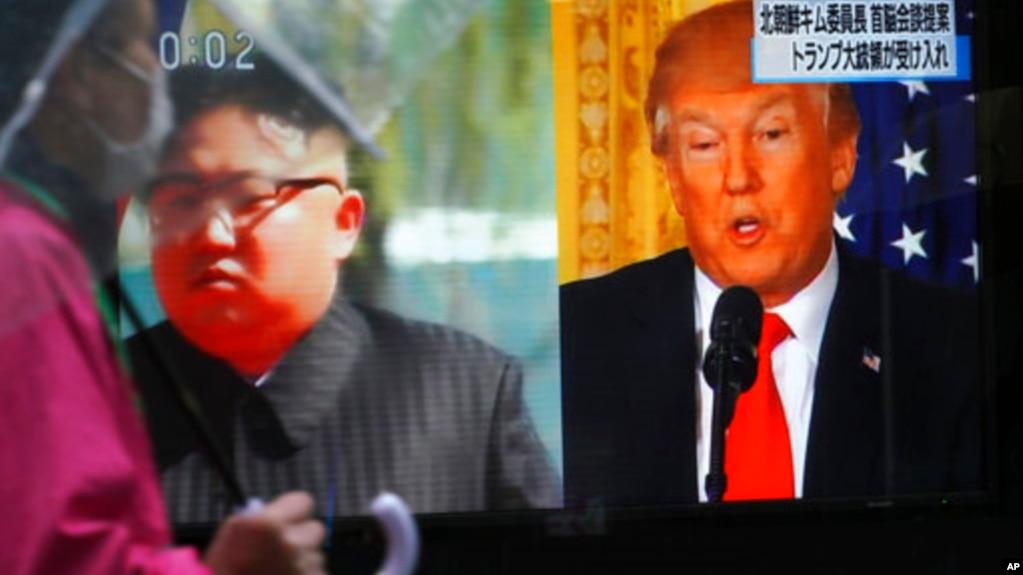 一名男子走过东京街头正在播放美国总统川普(右)和朝鲜领导人金正恩画面的电视屏幕。(2018年3月9日)