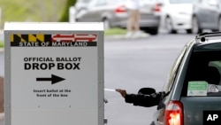 A motorist drops off a mail-in ballot outside of a voting center during the 7th Congressional District special election, Tuesday, April 28, 2020, in Windsor Mill, Md. (AP Photo/Julio Cortez)