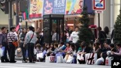 Para turis China beristirahat di pinggir jalan setelah berbelanja di daerah pertokoan mewah Ginza di Tokyo. (Foto: Dok)