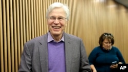 FILE - Finnish Professor Bengt Holmstrom of the Massachusetts Institute of Technology smiles as he departs a news conference after speaking to members of the media on the campus of MIT in Cambridge, Massachusetts, Oct. 10, 2016.