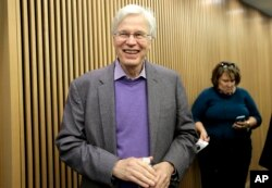 Finnish Professor Bengt Holmstrom of the Massachusetts Institute of Technology smiles as he departs a news conference after speaking to members of the media, Oct. 10, 2016, on the campus of MIT in Cambridge, Mass.