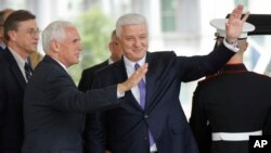 Vice President Mike Pence, left, with Prime Minister of Montenegro Dusko Markovic, center, wave to members of the media outside the West Wing of the White House in Washington, June 5, 2017.