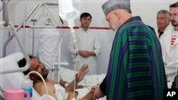 ប្រធានាធិបតីអាហ្វហ្គានីស្ថាន Hamid Karzai សន្ទនាជាមួយអ្នកត្រូវរបួសនៅក្នុងការផ្ទុះគ្រាប់បែកអត្តឃាត នៅក្នុងពេលដែលលោកទៅសួរសុខទុក្ខក្នុងមន្ទីរពេទ្យសង្គ្រោះបន្ទាន់ក្នុងទិក្រុងកាប៊ុលនៅថ្ងៃទី៧ ខែធ្នូ ឆ្នាំ២០១១នេះ។