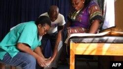 Un technicien rejoint Adjovi Koudahe avec un nouveau support prothétique imprimé en 3D au CNAO (centre national d'orthopédie et de physiothérapie du Togo) à Lomé, le 19 juin 2018.
