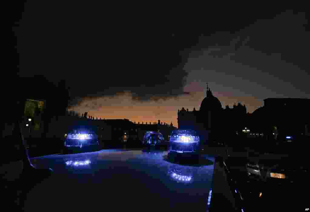 Carabinieri (Italian paramilitary police) car's blue lights flash in front of St. Peter's Basilica, in Rome, Italy. Extra pilgrims and tourists coming for the Holy Year, which runs through Nov. 20, 2016, pose challenging logistics for both Vatican and Italian security forces.