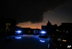 Carabinieri (Italian paramilitary police) car's blue lights flash in front of St. Peter's Basilica, in Rome, Italy, Dec. 4, 2015.