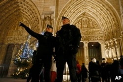 French Police officers stand near the entrance of Notre Dame Cathedral as worshippers arrive for the Christmas eve mass in Paris, France, Dec. 24, 2016. Security was tightened at Christmas across Europe after a deadly truck attack on a market in Berlin.