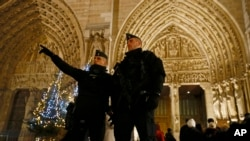 French Police officers stand near the entrance of Notre Dame Cathedral as worshippers arrive for the Christmas eve mass in Paris, Dec. 24, 2016. Security was tightened at Christmas across Europe after a deadly truck attack on a market in Berlin.