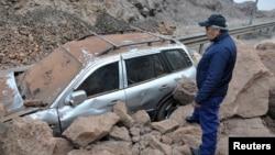 Một nhân viên cứu hộ đứng cạnh chiếc xe bị kẹt trong đất đá sau trận động đất ở Iquique, Chile, 2/4/14
