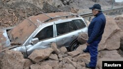 A rescue worker inspects a car caught under a landslide after an earthquake and tsunami hit the northern port of Iquique, Chile, April 2, 2014.