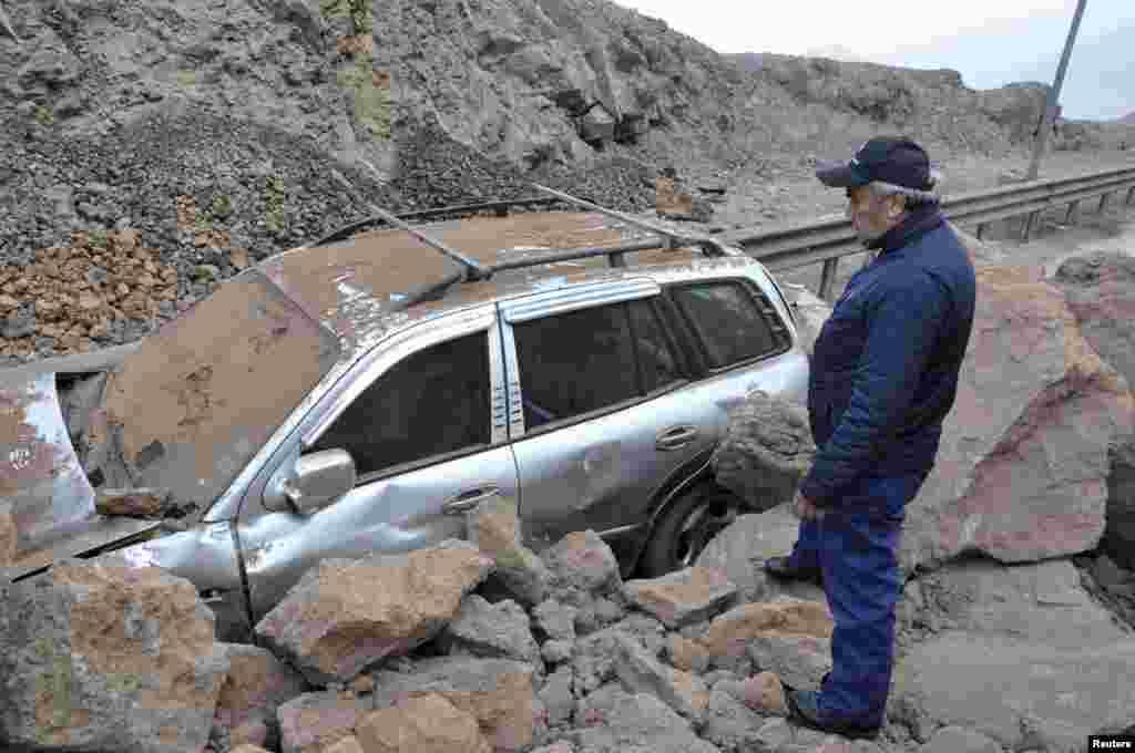 Seorang petugas penyelamat memeriksa mobil yang terperangkap dalam tanah longsor akibat gempa dan tsunami yang melanda pelabuhan Iquique di Chile utara (2/4).