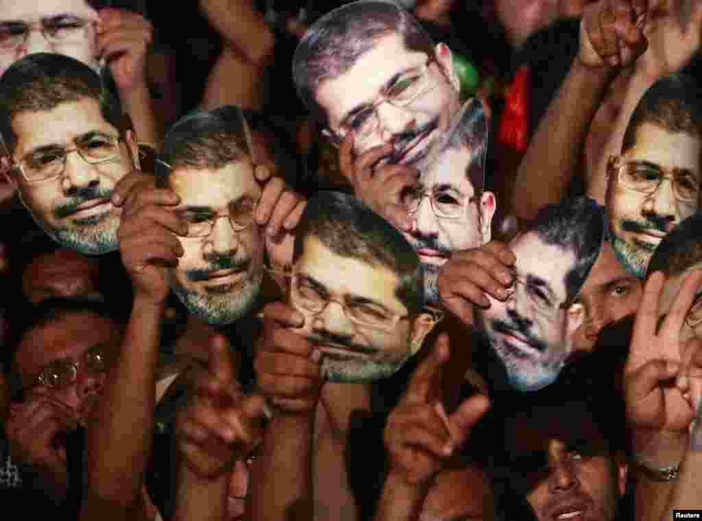 Members of the Muslim Brotherhood and supporters of deposed Egyptian President Mohamed Morsi hold up masks of him as they gather at the Rabaa Adawiya square, where they are camping, in Cairo, July 13, 2013.