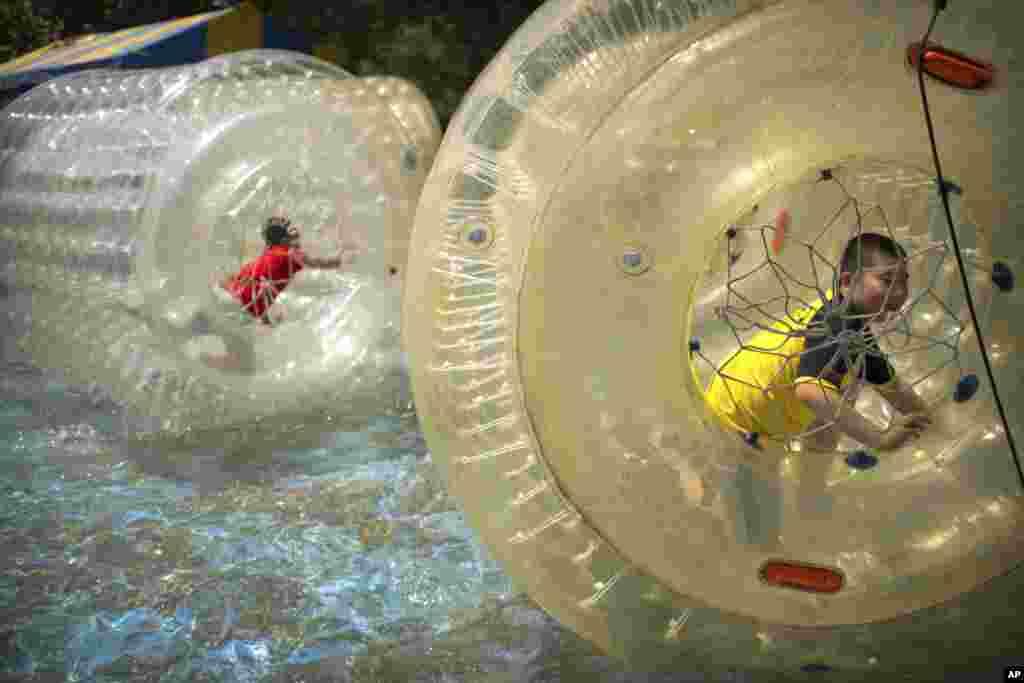 2017年6月1日,在北京的一座公园内,孩子们在水上的大型气球中玩耍。
