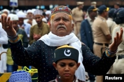 FILE - A man offers Eid al-Fitr prayers marking the end of the holy fasting month of Ramadan outside a railway station, in Mumbai, India, June 16, 2018.