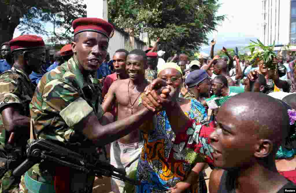 People greet soldiers as they celebrate in Bujumbura, May 13, 2015. Crowds poured onto the streets of Burundi's capital to celebrate after a general said he was dismissing President Pierre Nkurunziza for violating the constitution by seeking a third term in office, a Reuters witness said.
