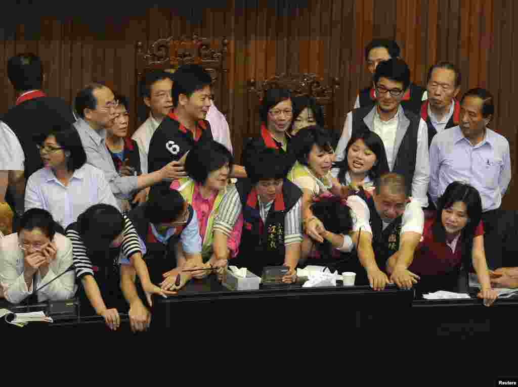 Opposition Democratic Progressive Party legislators (in green vests) scuffle with ruling Nationalist Party legislators (in black vests) at the Legislative Yuan in Taipei, Taiwan.