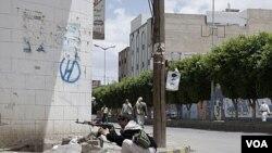 Pendukung kepala suku Hashid siaga dengan senjata AK-47 dalam bentrokan dengan pasukan pemerintah Yaman di Sana'a (24/5).