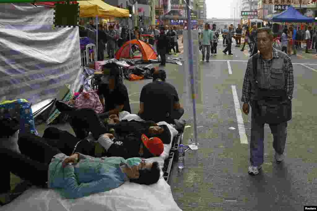 A resident walks past pro-democracy demonstrators resting while they occupy a street in the Mong Kok shopping district of Hong Kong, Nov. 19, 2014.