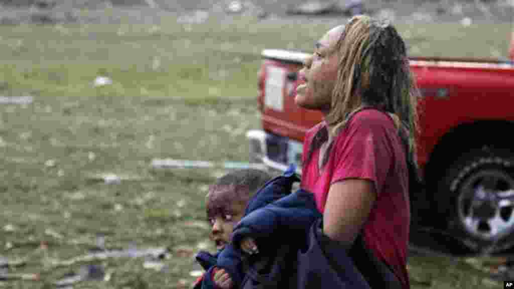 A woman carries an injured child to a triage center near the Plaza Towers Elementary School in Moore, Okla., Monday, May 20, 2013.