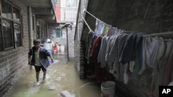 Ocatvio Diaz wades through sewage water flooding his home's patio after the Remedios sewage river overflowed on the outskirts of Mexico City, Mexico, July 1, 2011
