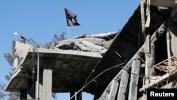Zastava militanata Islamske države uslikana iznad uništene kuće u blizini Skvera sata u Raki, Sirija, 18. oktobra 2017.