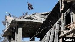 拉卡一座破损的建筑物上飘扬着一面伊斯兰国组织的旗帜