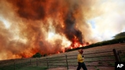 Emergency crews battle a running wildfire that is threatening a home on April 19, 2011 in Strawn, Texas.