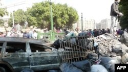 Một chiếc xe hơi bị cháy, hàng đống gạch đá và rác ở Quảng trường Tahrir sau cuộc biểu tình