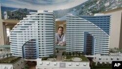 Seorang broker berpose di belakang model sebuah kondo-hotel. Konsep kondo-hotel saat ini semakin populer dalam industri hotel/penginapan.