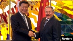Cuba's President Raul Castro, right, shakes hands with China's President Xi Jinping during a meeting at Revolution Palace in Havana, Cuba, July 22, 2014.