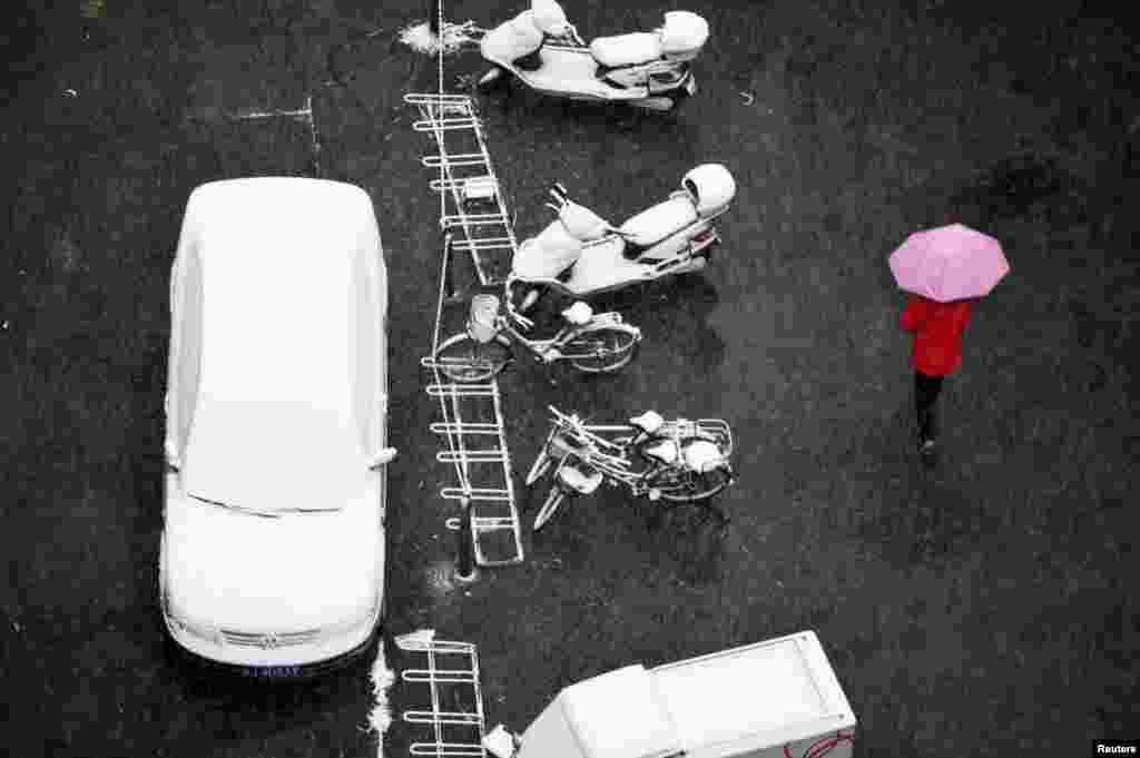 A person holds an umbrella while walking past parked vehicles as it snows in Beijing, China.