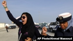 "FILE - Bahraini opposition activist Zainab al-Khawaja, left, gestures as she shouts ""God is greater than any tyrant,"" while being arrested by police officers in Bahrain, Oct. 21, 2012."
