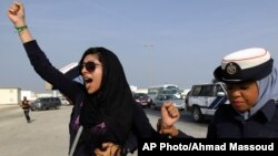 """FILE - Bahraini opposition activist Zainab al-Khawaja, left, gestures as she shouts """"God is greater than any tyrant,"""" while being arrested by police officers in Bahrain, Oct. 21, 2012."""