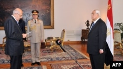A handout picture released by the Egyptian Presidency shows Egyptian leader Mohamed ElBaradei (L) being sworn in as Egypt's interim vice president for foreign relations, in front of Egypt's interim president Adly Mansour (R), in Cairo on Jul. 14, 2013.