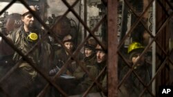 Ukrainian coal miners wait in a room before going underground at the Zasyadko mine in Donetsk, Ukraine, March 4, 2015.