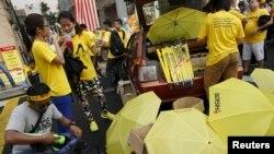 "FILE - People sell umbrellas to supporters of pro-democracy group ""Bersih"" (Clean) near Dataran Merdeka in Malaysia's capital city of Kuala Lumpur, Aug. 30, 2015."