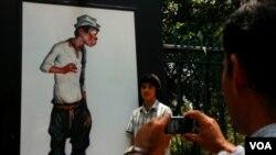 """Un joven posa para sacarse una fotografía al lado de la caricatura del """"peladito"""" más conocido de México."""