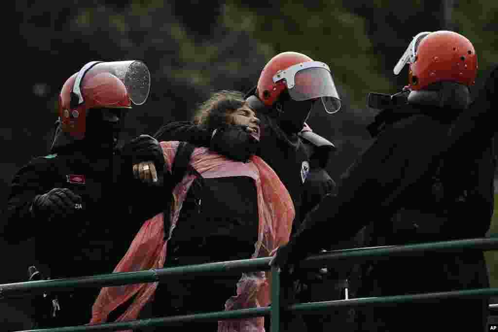 Cảnh sát Tây Ban Nha bắt giữ bà Urtza Alkorta, một nhà hoạt động của tổ chức vũ trang ETA của người Basque, trong lúc bà quấn người bằng bao nhựa màu hồng, đứng trên một cái cầu cùng với hàng trăm người ủng hộ ở Ondarroa, miền bắc Tây Ban Nha.
