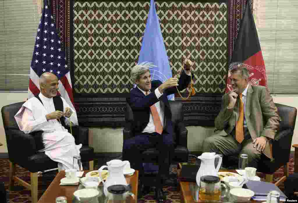 U.S. Secretary of State John Kerry (center) holds up a string of Islamic beads, as Afghanistan's presidential candidate Ashraf Ghani Ahmadzai (left) and Jan Kubis, the U.N. Secretary-General's special representative look on, during a meeting at the U.S. embassy in Kabul, Aug. 8, 2014.