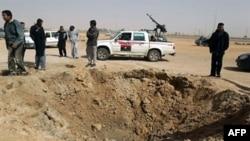 Phe nổi dậy Libya đứng cạnh một hố bom sau một vụ oanh kích của lực lượng Gadhafi ở Ajdabiya