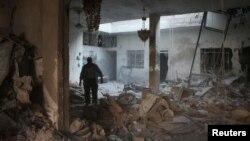 Serangan udara pasukan Suriah menghancurkan bangunan di kota Arbin (25/7).