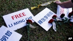 FILE - Roses and slogans reading ''Free Lee Ming-che'' are placed on the lawn during a media event to support Taiwanese activist Lee Ming-che detained in China, in Taipei, Taiwan, Nov. 28, 2017.