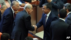 Ismet Yilmaz, the ruling Justice and Development Party's candidate and the Defense Minister in the outgoing government (C-R) shakes hands with the Nationalist Movement Party leader Devlet Bahceli at the Parliament after his election as the new Speaker in Ankara, July 1, 2015.