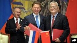 2014年5月21日俄羅斯總統普京(左)、俄羅斯天然氣工業股份公司首席執行官阿列克謝•米勒(中)與中國石油集團主管周吉平在中國上海中俄天然氣協議簽字儀式上