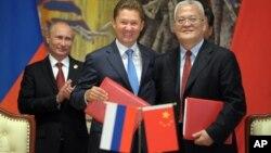 2014年5月21日俄罗斯总统普京(左)、俄罗斯天然气工业股份公司首席执行官阿列克谢·米勒(中)与中国石油集团主管周吉平在中国上海中俄天然气协议签字仪式上